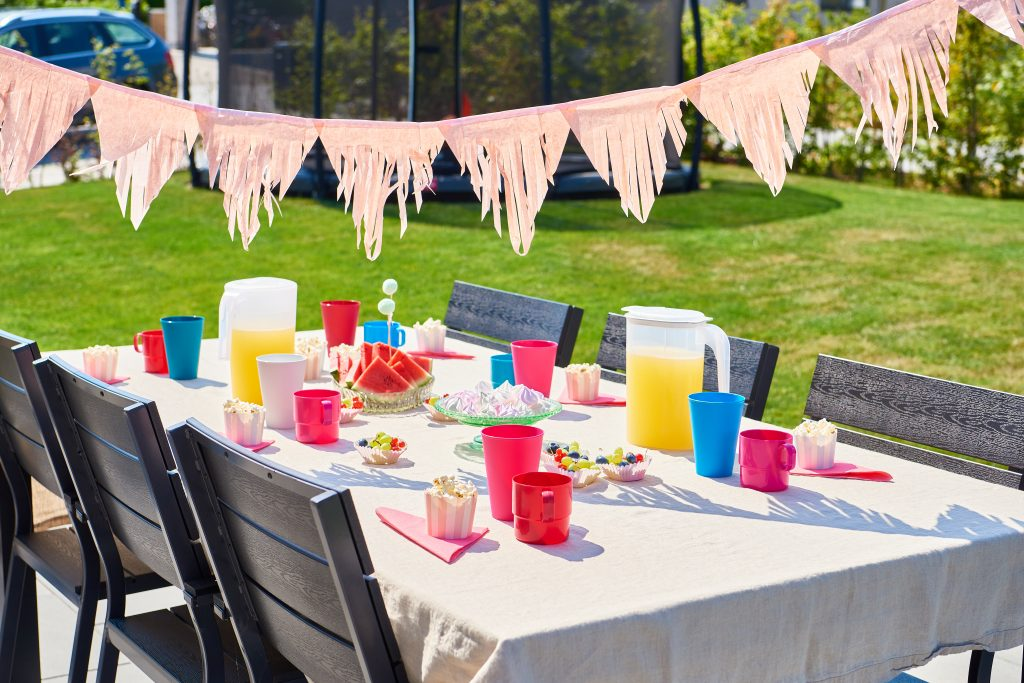 Drinking category assortment that consist of jugs, mugs, plastic glasses that, are convinient to use one every occassion like party. Some of products in various shapes and colors stands on the table in garden.