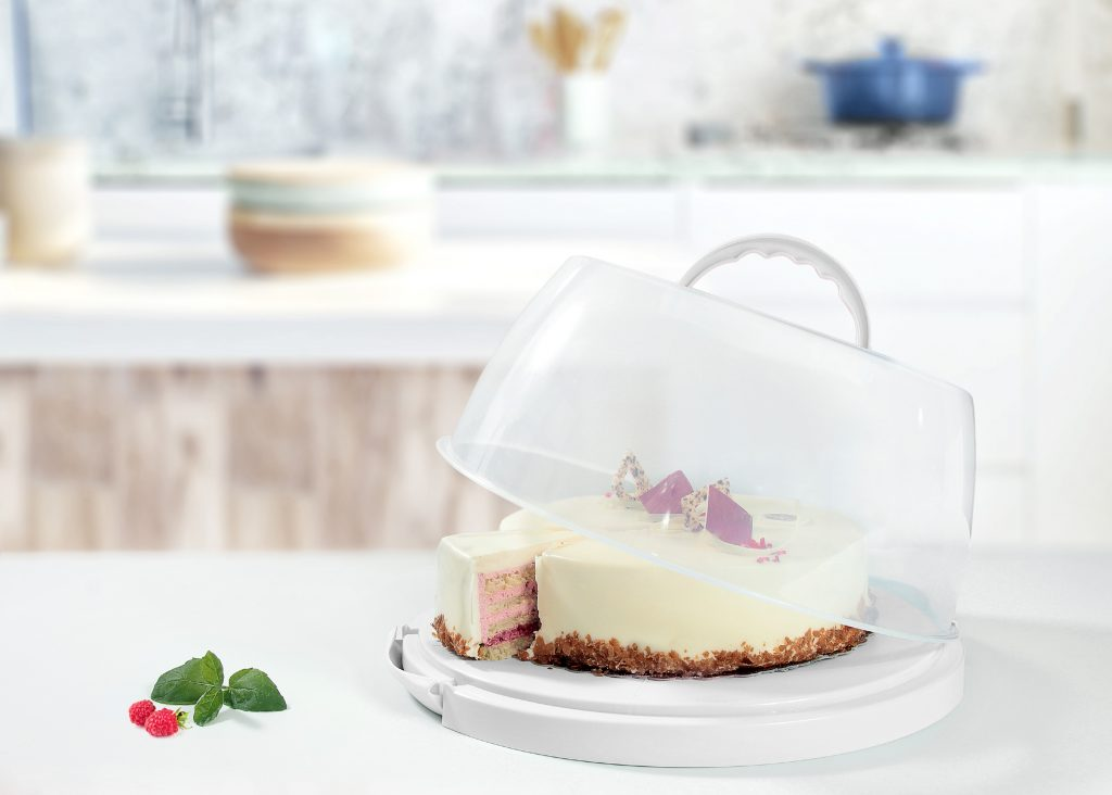 Cake Box, perfect for storage, transport and serving cakes. It is part of Food Preparation category consiting practical kitchen tools. Cake Box stands on a tabletop in a kitchen.