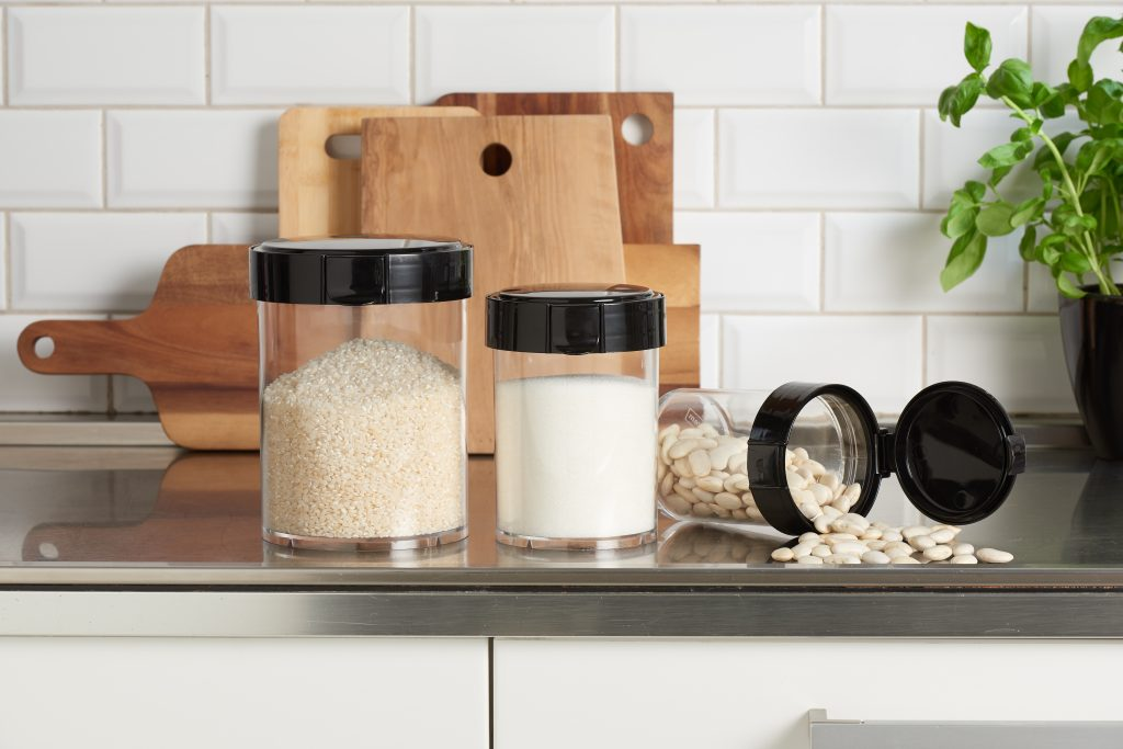 Mary is a series of cylindrical dry food storage containers. They have a screw-off lid closed by a small tap in the front. Three canisters are on the tabletop, one of them lies and it is open.