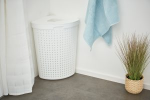 Seoul Laundry basket in the variant that fits into the corner. It complements the Seoul series while maintaining a modern Scandinavian design. The white basket stands in the bathroom with two towels hanging next to it.