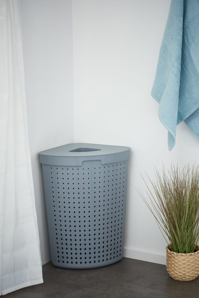 Seoul Laundry basket is a stylish and practical solution for a bathroom. It complements the Seoul series. The basket in a Tradewinds color stands in the bathroom with two towels hanging next to it.