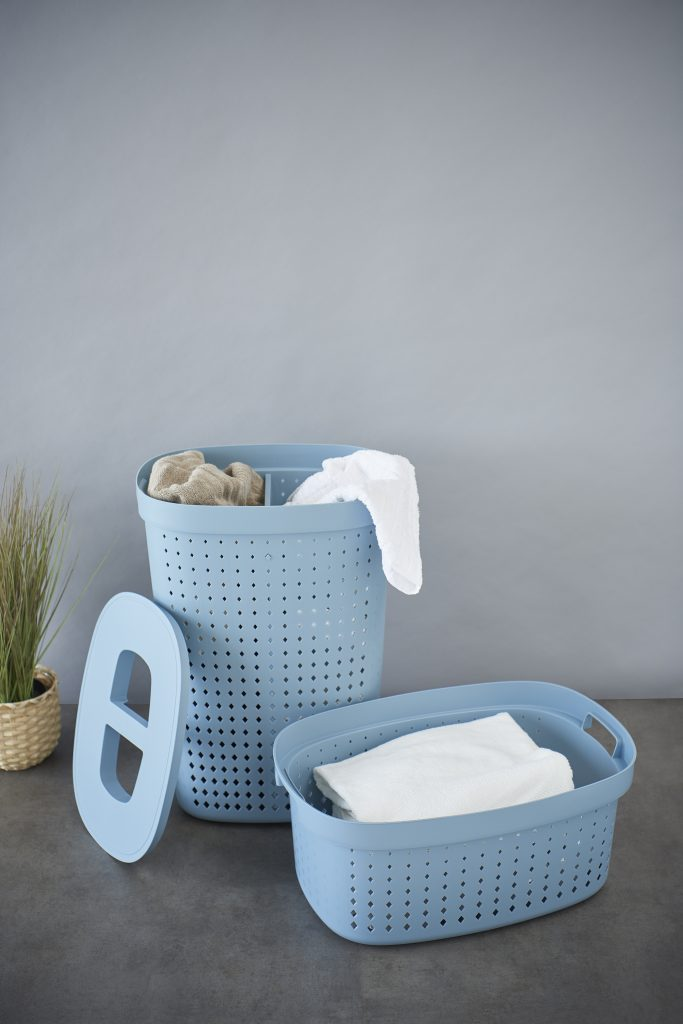 A laundry basket and a linen basket set for every need. The first one has a separator for two different types of laundry. Both baskets are oval and in Faded denim color. They stand on the floor with laundry inside.
