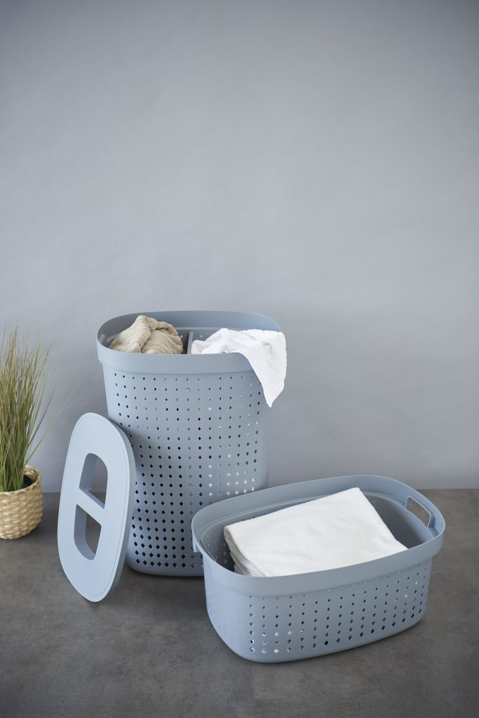 A laundry basket and a linen basket set for every need. The first one has a separator for two different types of laundry. Both baskets are oval and in Tradewinds color. They stand on the floor with laundry inside.