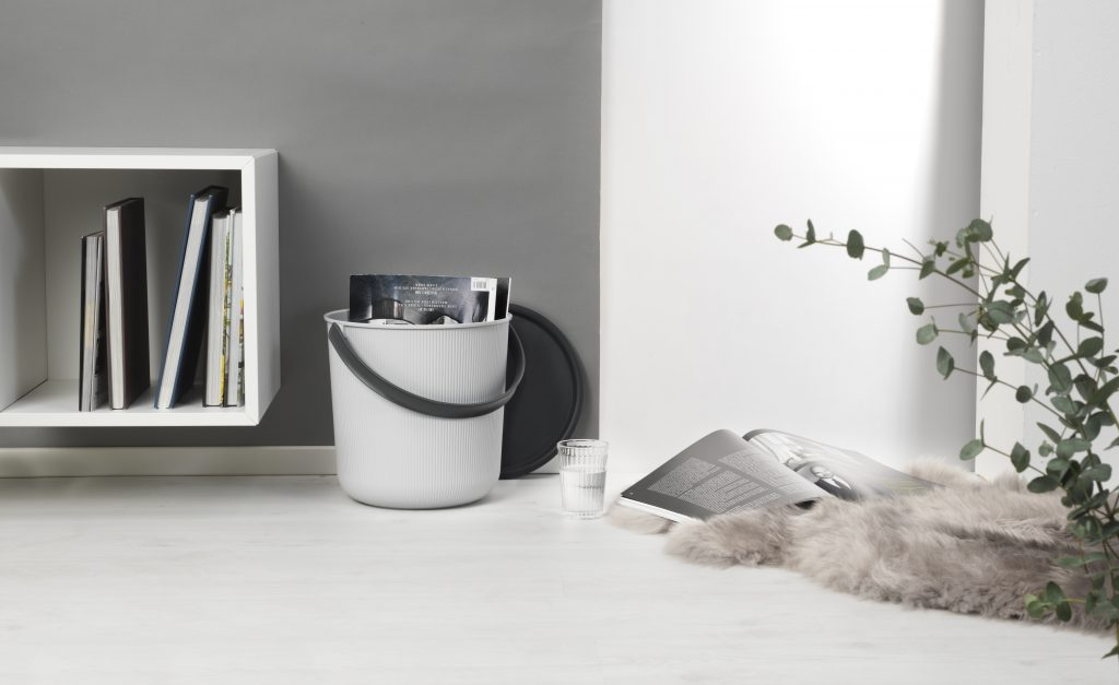 Modern Akita storage bucket with an elegant design, made from post-consumer recycled material. Bucket stands near the wall, next to bookcase.