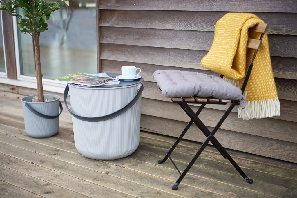 Akita storage bucket has a completly flat lid which can transform bucket in a coffee table. Buckets in two different sizes stands on the terrace.