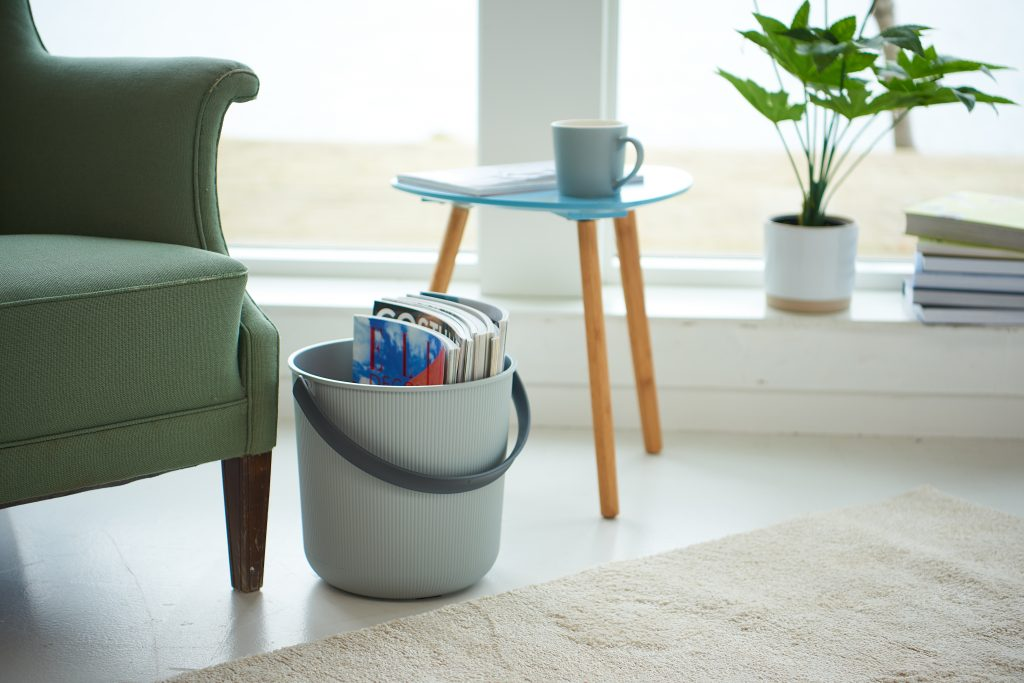 Akita storage buckets available in two sizes are great to store books or journals inside. A bucket is in a living room near the armchair and table.