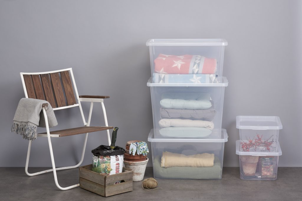 Basic Box storage boxes, available in various sizes are the best to store blankets, pillow, and other stuff related to the garden. Containers are stacked vertically in two piles, that stand near the garden chair on the terrace.