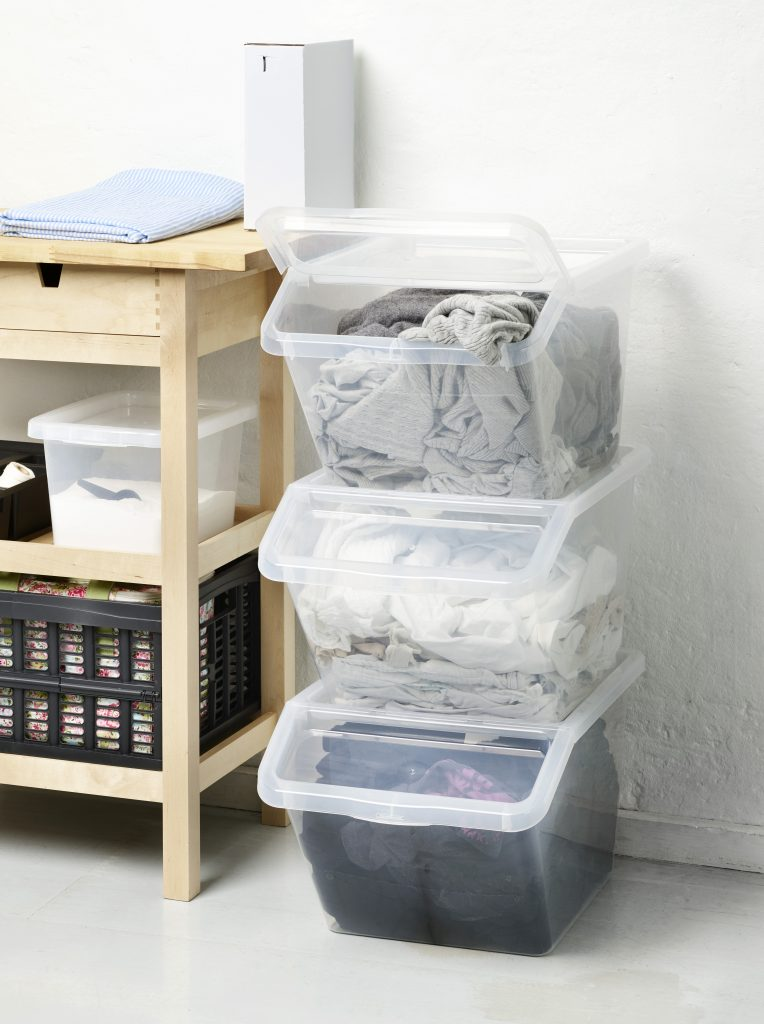 Slanded variant of Basic Box is ideal choice to organize, sort and store your laundry. Three boxes are stacked in pile near bathroom sink.