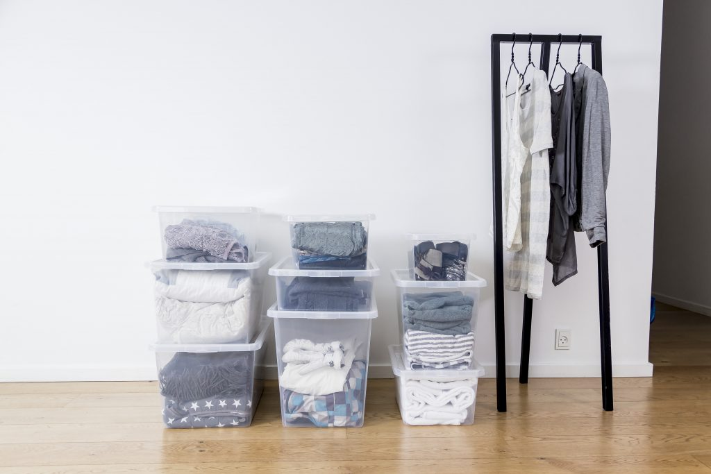 Basic Box container gives a perfect overview of clothes, curtains and others, stored inside due to transparent material. Nine containers of different sizes are full of clothes and stacked under the wall in three vertical piles.
