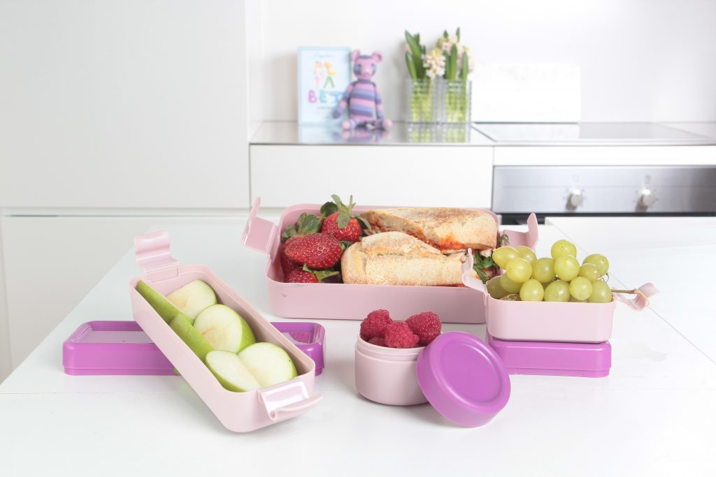 Hilo, series of lunch boxes in various shapes ideal for mixing different kinds of lunch and bringing afternoon snack. Pink variant of series stands on the tabletop.