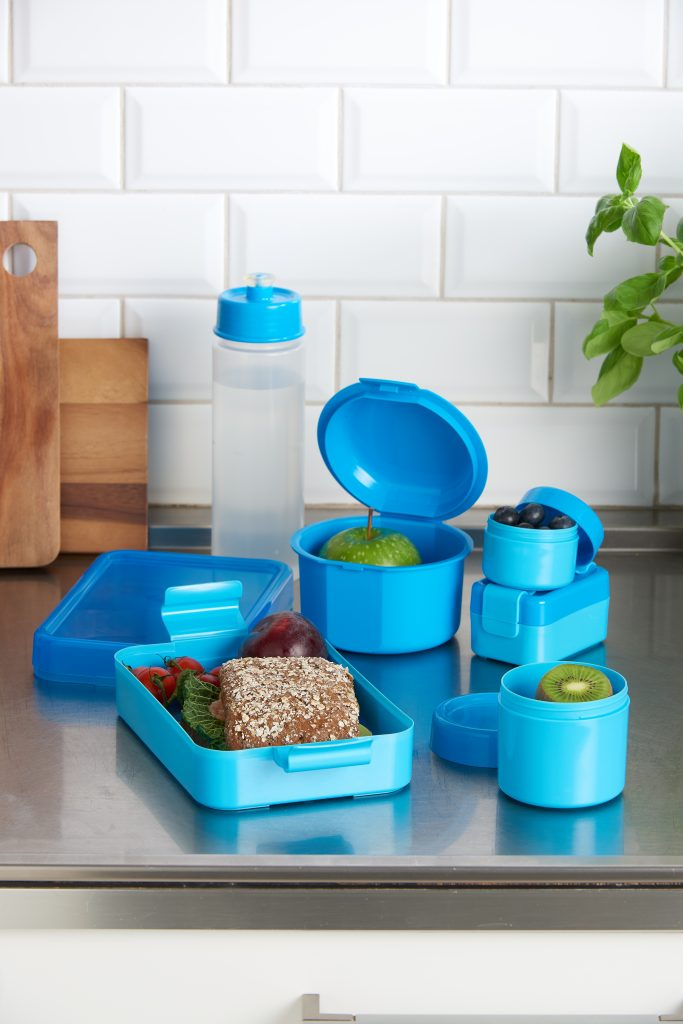 Hilo, series of lunch boxes and drinking bottles designed for kids and teens. Blue variant of series stands on the tabletop.