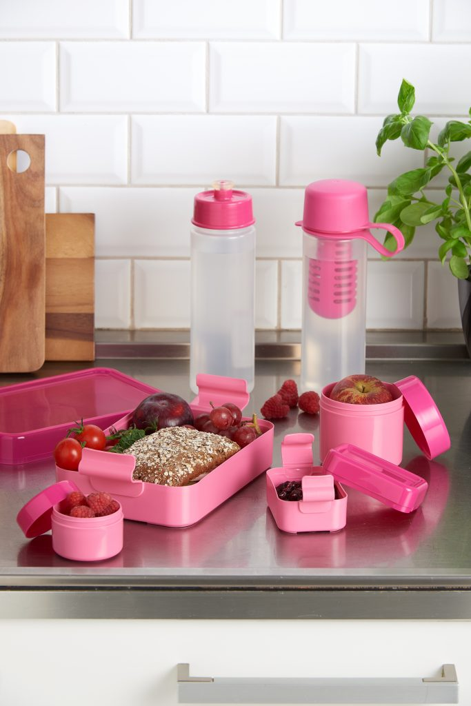 Hilo, series of lunch boxes and drinking bottles designed for kids and teens. Pink variant of series stands on the tabletop.