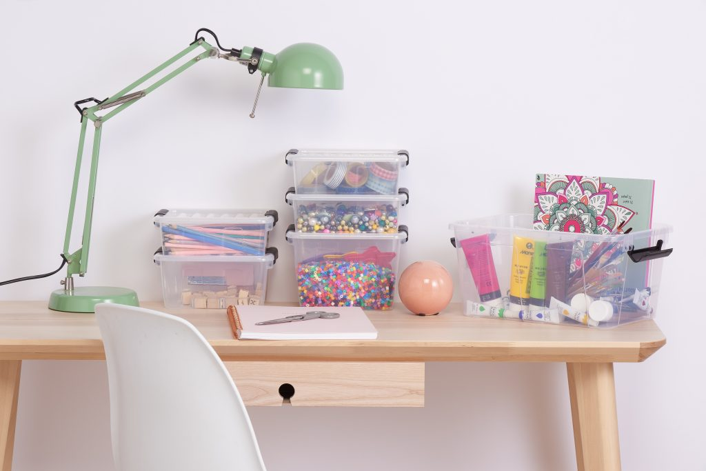 Home Box containers made of clear material, with clip-closed lid are a perfect solution for crafting items storage. Boxes full of crafting accessories are stacked horizontally in a few piles, which stand one by one on the desk.