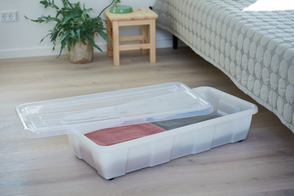 Bedroller Easy is a perfect underbed storage due to wheels and low profile connected with clip-on lid and semitranslucent material. The container filled with blankets stays near the bed and has a lid opened.