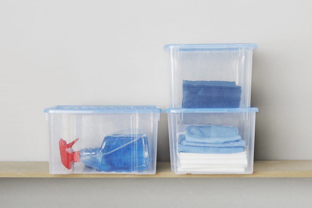 K-Box translucent storage boxes with blue clip-on lid are perfect for cleaning accessories storge. Two boxes are stacked vertically and one stands next to them on a shelf.