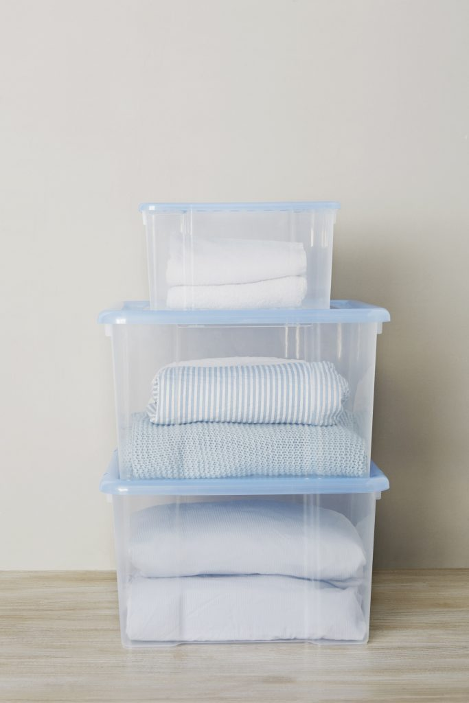 K-Box translucent storage boxes in two different sizes are perfect for towel and bedclothes storage. Three boxes are stacked in a vertical pile on the floor with some materials inside.