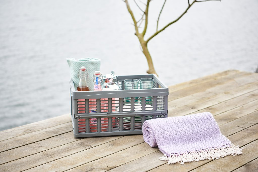 A Folding Box holder is a stylish and convenient picnic solution. Foldability and stackability allow saving space. Grey Folding Box full of picnic equipment stands and a table outside.