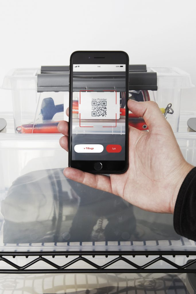 Two stackable translucent Probox clip-closed storage boxes, equipped with QR codes to help organize your storage. A hand is holding a phone and scanning one of the codes.