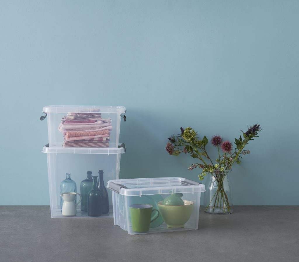 Stackable Probox translucent storage boxes in two different sizes with clip-closed lids and QR codes, to organize storage. Boxes are used as household storage placed on the floor near a vase with dried flowers.