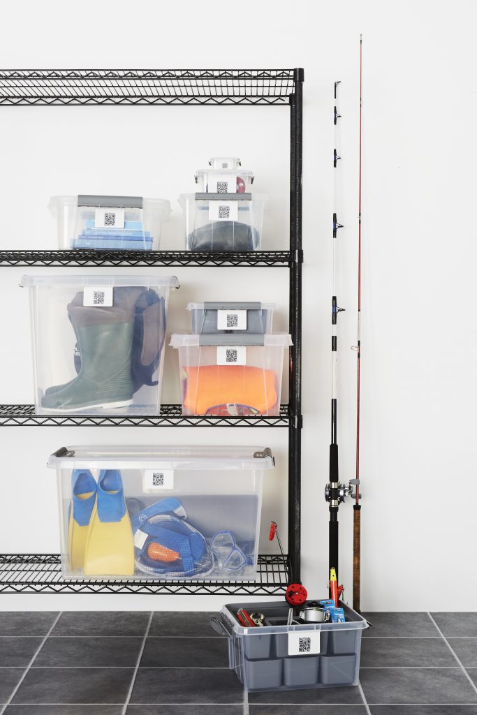 Stackable, translucent Probox storage boxes in five various sizes, with QR codes and Inserts to organize storage. Boxes are placed on and near the rack and used as watersport equipment storage in the garage.