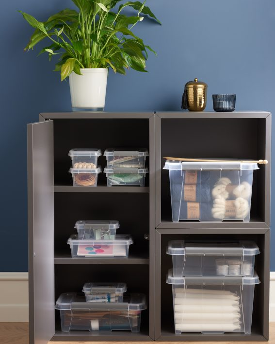 Stackable translucent Probox clip-closed storage boxes in four different sizes, with QR codes to organize storage. Boxes are placed inside a cupboard and used to store crafting household items.