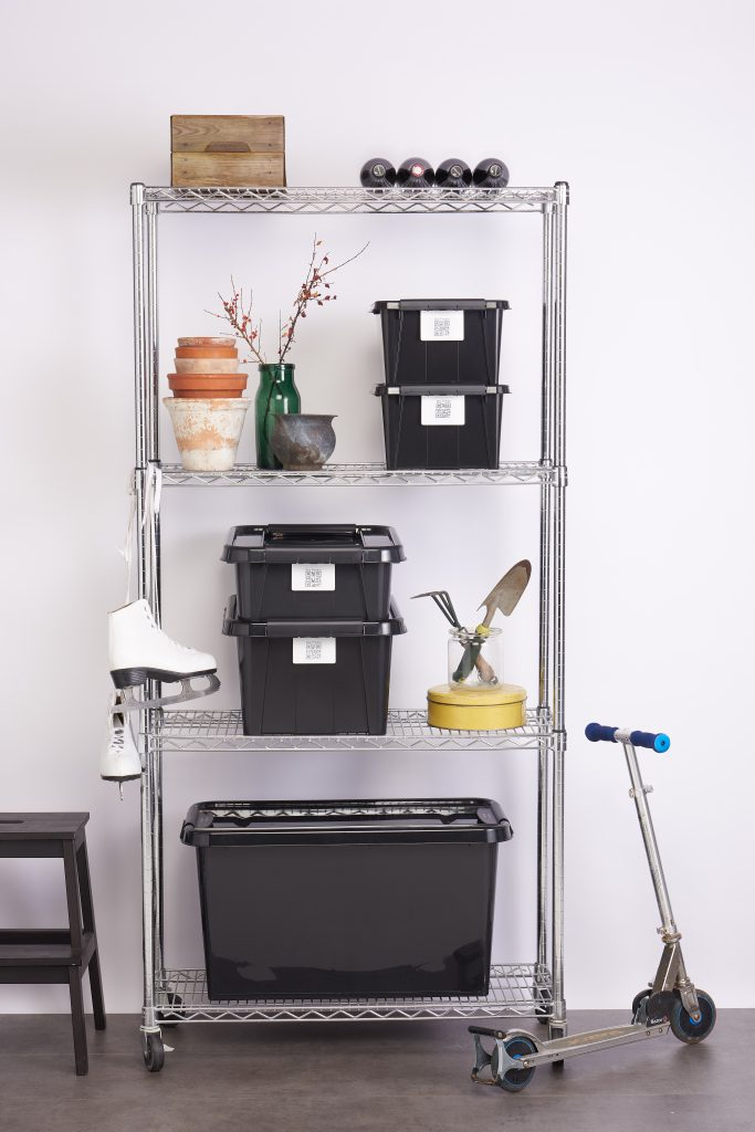 Five stackable Probox Recycle storage boxes made of recycled PP are in four different sizes, equipped with QR codes that help organize your storage. Boxes are placed on metal shelves, sport and gardening equipment is visible.