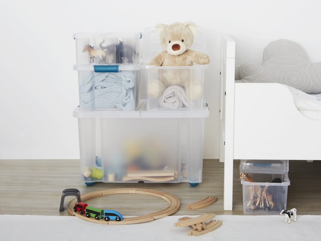 Five stackable Sanshui storage boxes with clip-closed lids stacked on top of each other and used as playroom storage.