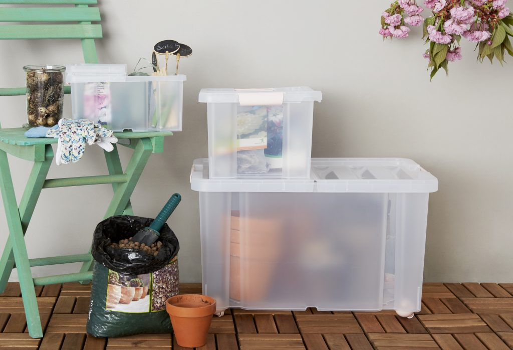 Three Sanshui clip-closed storage boxes in different sizes, two of them are stacked on top of each other and one is placed on the wooden chair, all are used as gardening items storage.