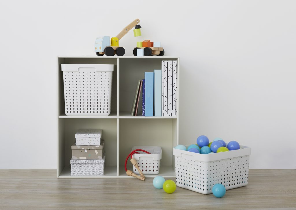 Three Seoul storage baskets in different sizes placed inside and near the bookcase, all are used as playroom storage.