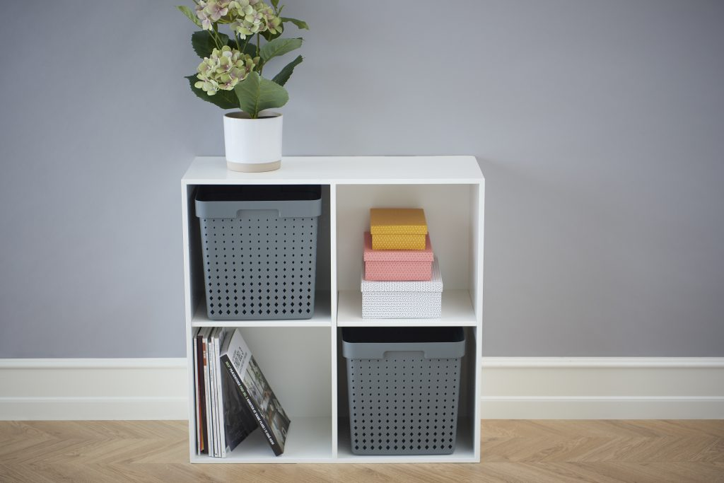 Extra-large Seoul storage baskets in grey color are placed in the bookcase in a living room.