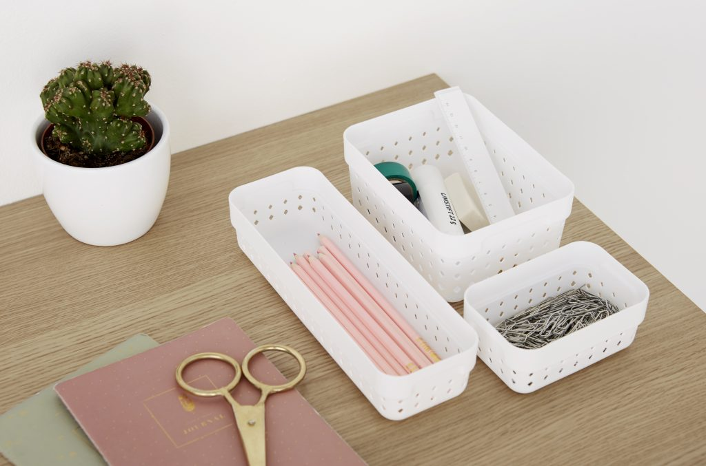 Three Seoul Organizers in white color are used to arrange pink stationery on the desk. The boxes are placed on the top of the tabletop.