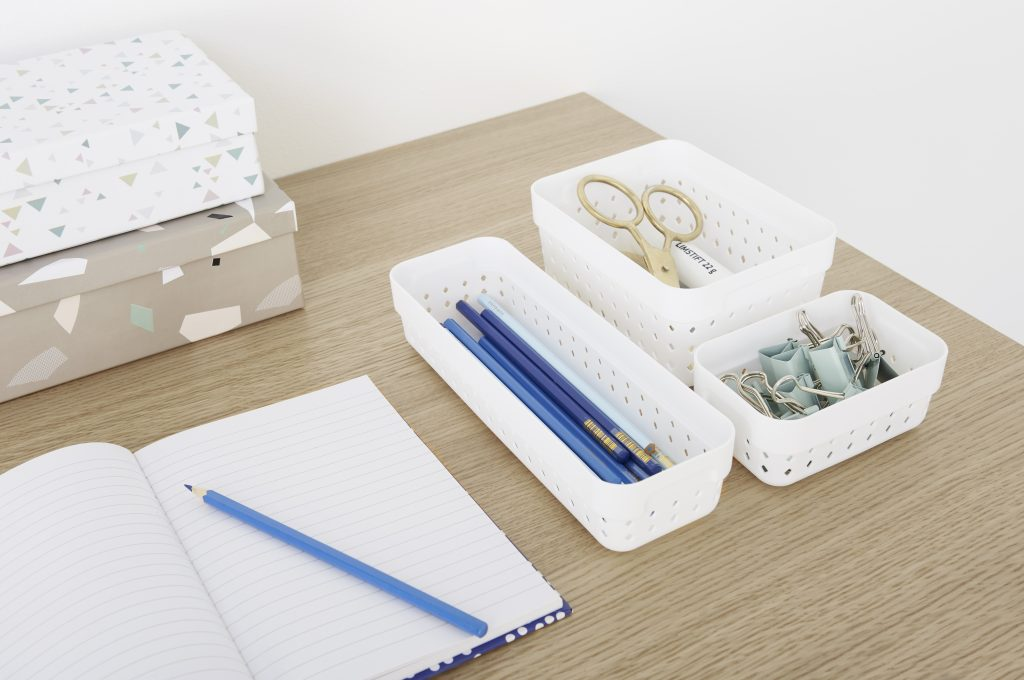 Three Seoul Organizers in white color are used to arrange blue stationery on the desk. Boxes are placed on side of the desk. The boxes are placed on the side of the tabletop.