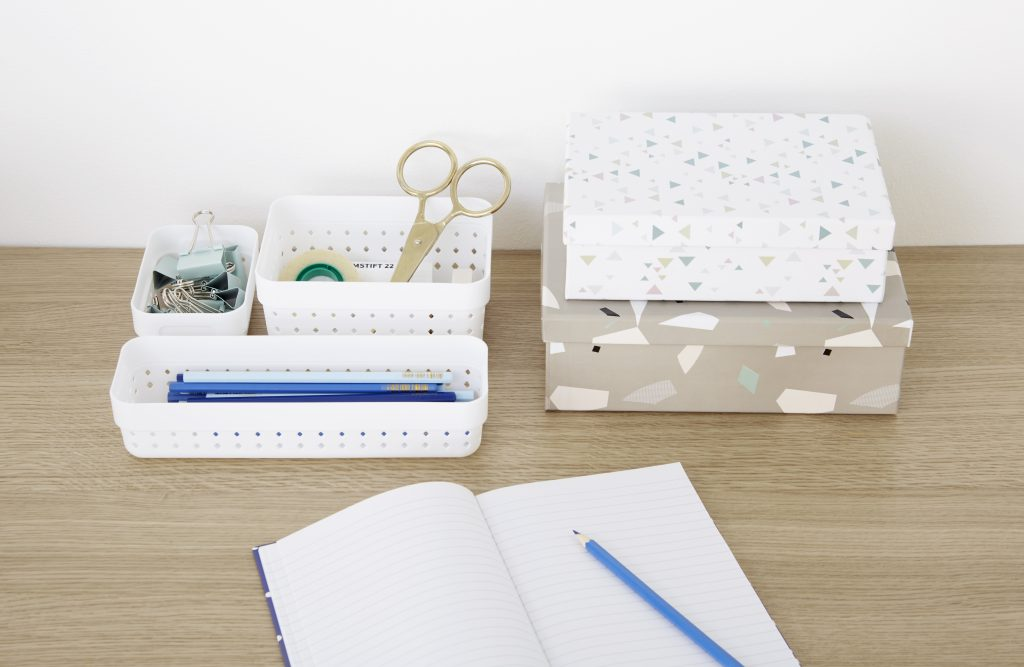 Three Seoul Organizers in white color are used to arrange blue stationery on the desk. The boxes are placed on the top of the tabletop.