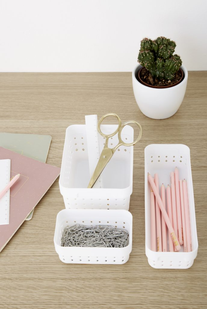 Three Seoul Organizers in white color are used to arrange pink stationery on the desk. The boxes are placed on the side of the tabletop.