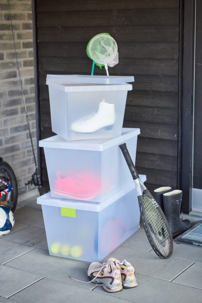 Semi-translucent practical boxes, which are part of the Tag Store series are stacked on top of each other and used as sports equipment storage.