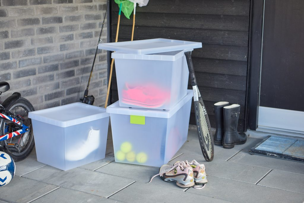 Semi-translucent practical boxes, which are part of the Tag Store series are stacked side by side and used as sports equipment storage.