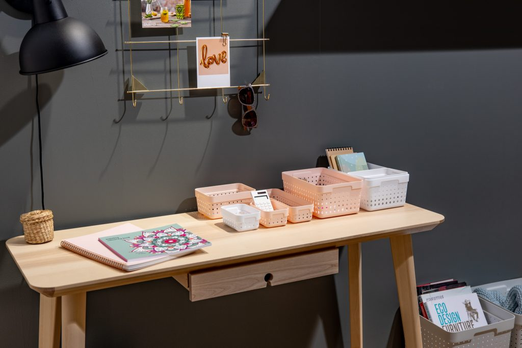 Seoul Organizers in different colors and sizes are used to organize desk. Baskets are placed on side of the desk.