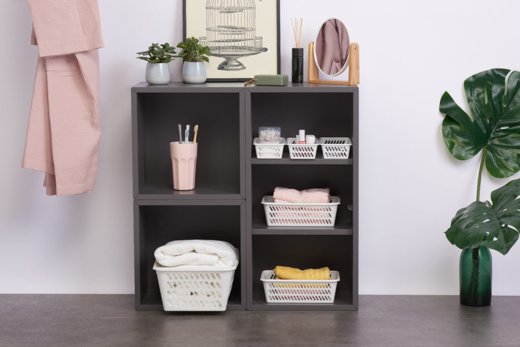 Classic Mini baskets in many various sizes are the perfect bathroom storage solution. Containers in 3 different sizes are placed inside a cupboard holding towels and other bathroom accessories.